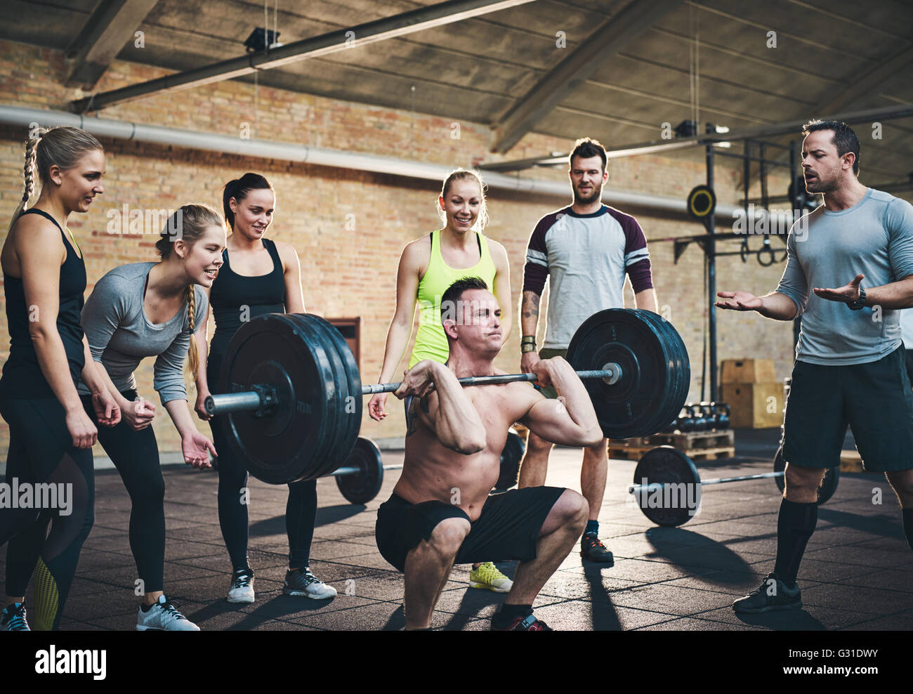 Fit man lifting barbells looking focused, working out in a gym with other people cheering him on in support - Stock Image