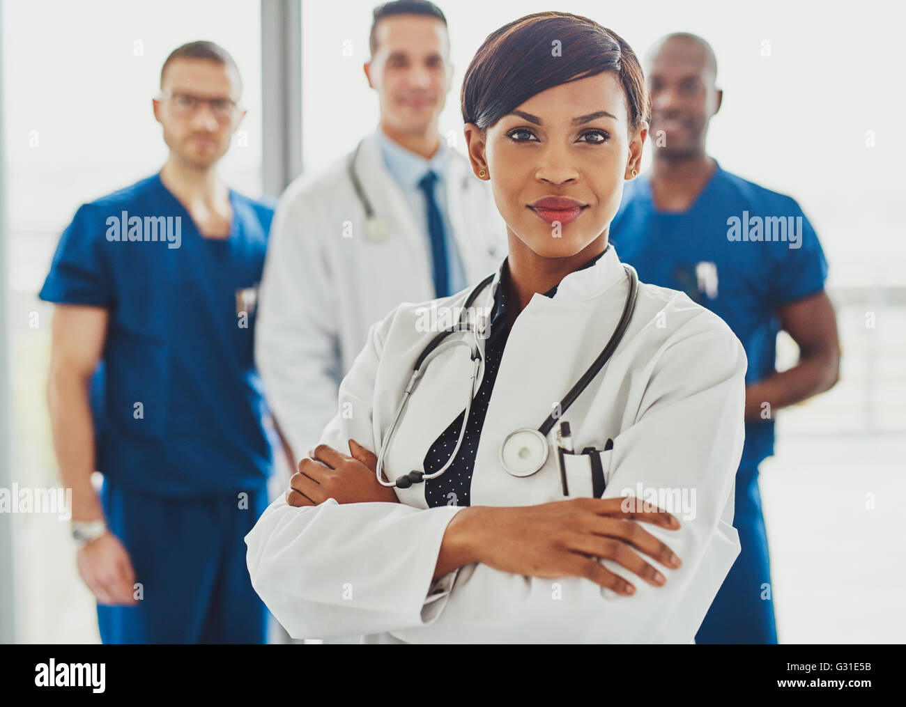 00e0e895ec0 Black female doctor in front of team, looking at camera with medical team  in background