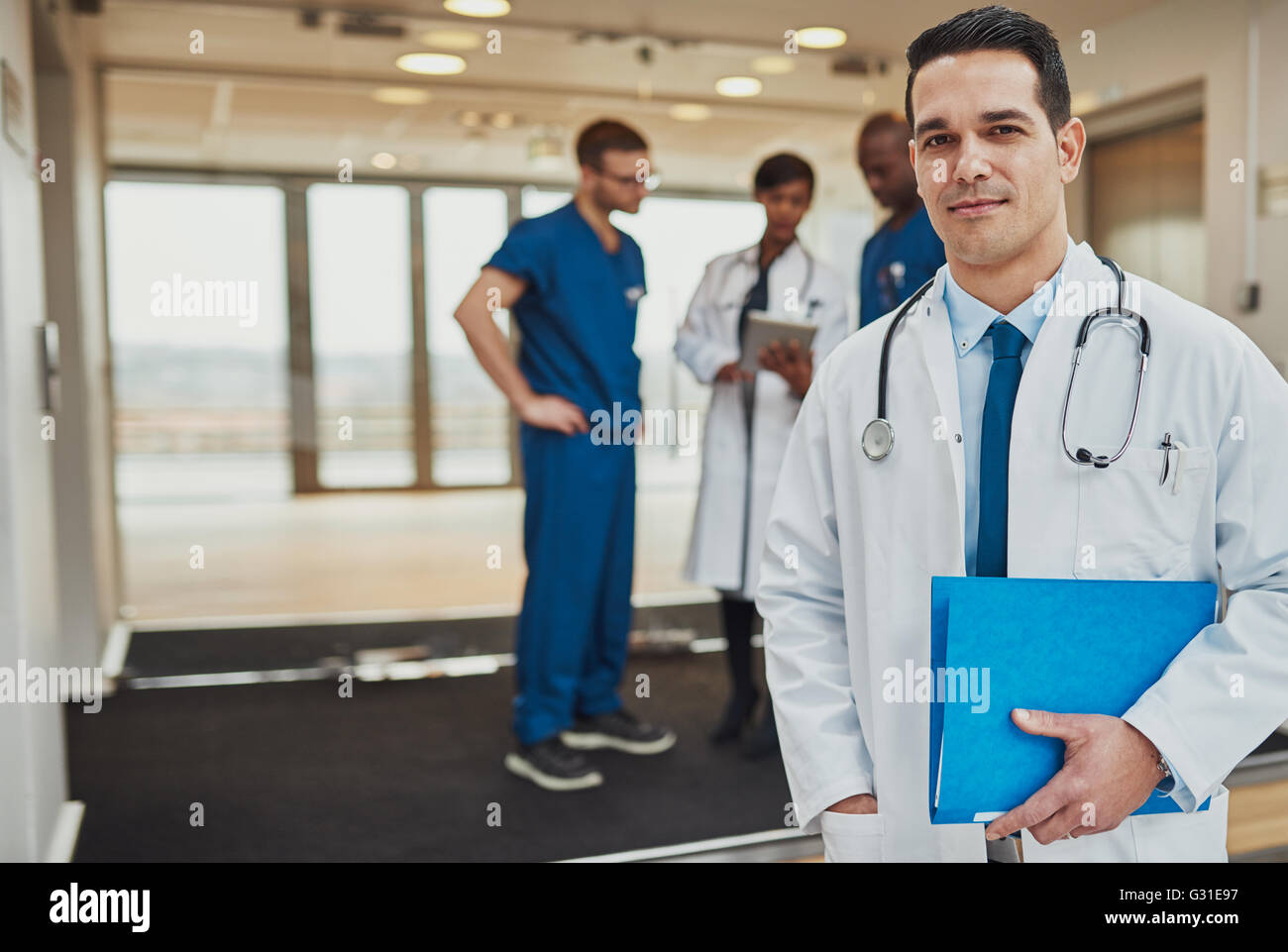 Doctor at hospital standing in front of team of surgeons and doctors, Medical Crew - Stock Image