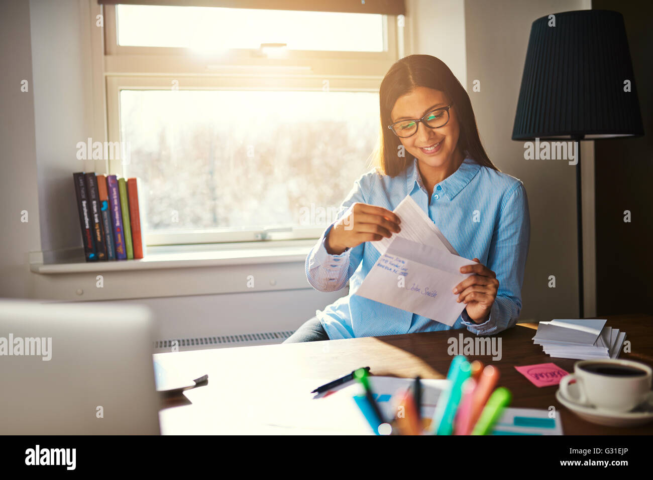 Business woman getting ready to mail a letter looking satisfied - Stock Image