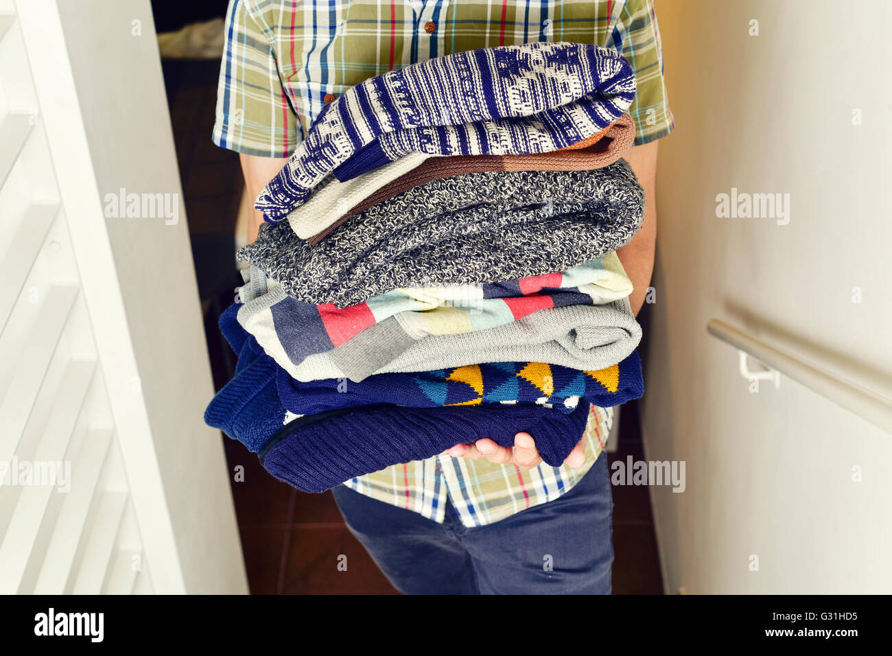 closeup of a young man wearing a short sleeved shirt carrying a pile of different folded sweaters Stock Photo