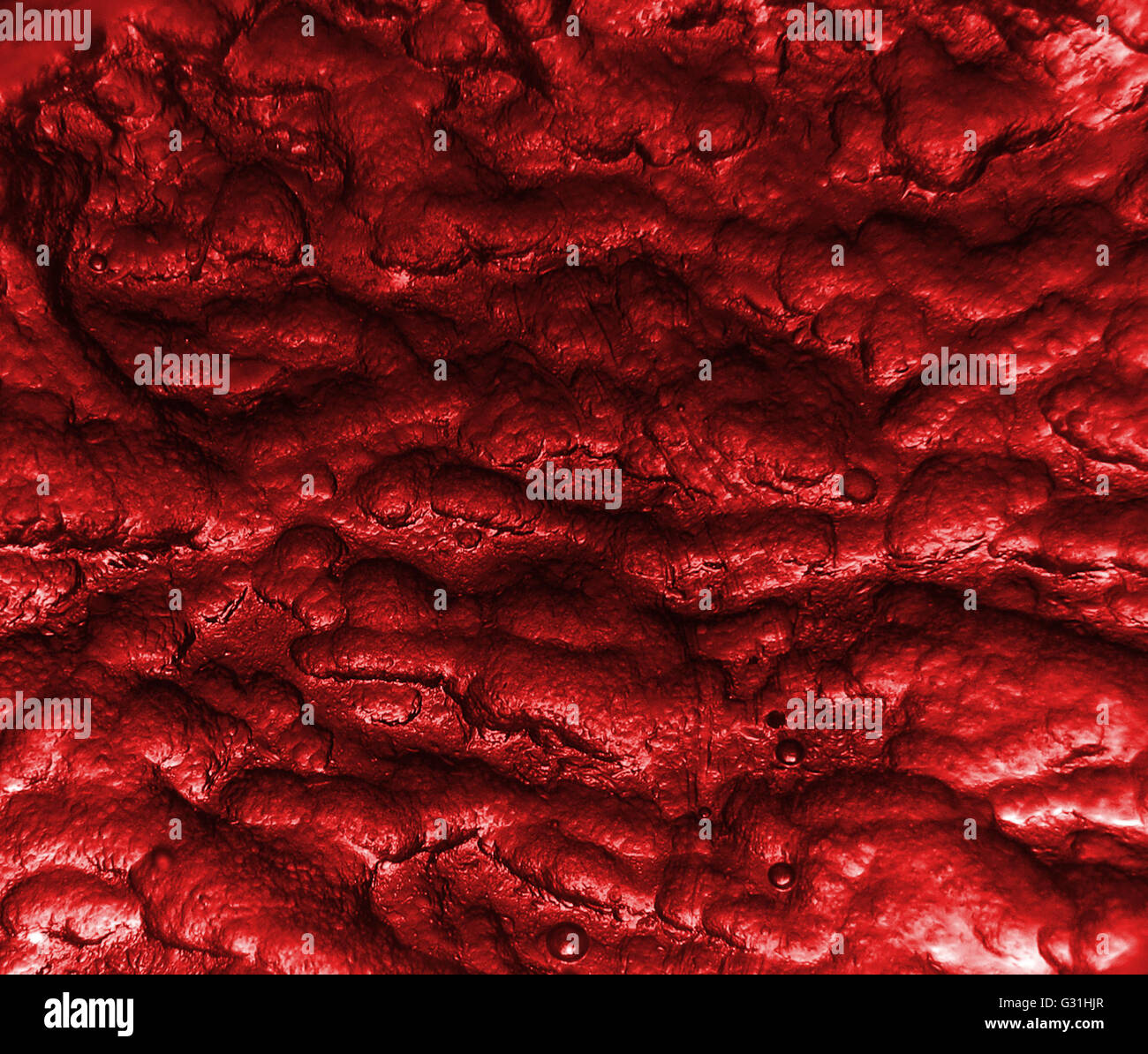 A background red texture with a weird texture and design with small bubbles. - Stock Image