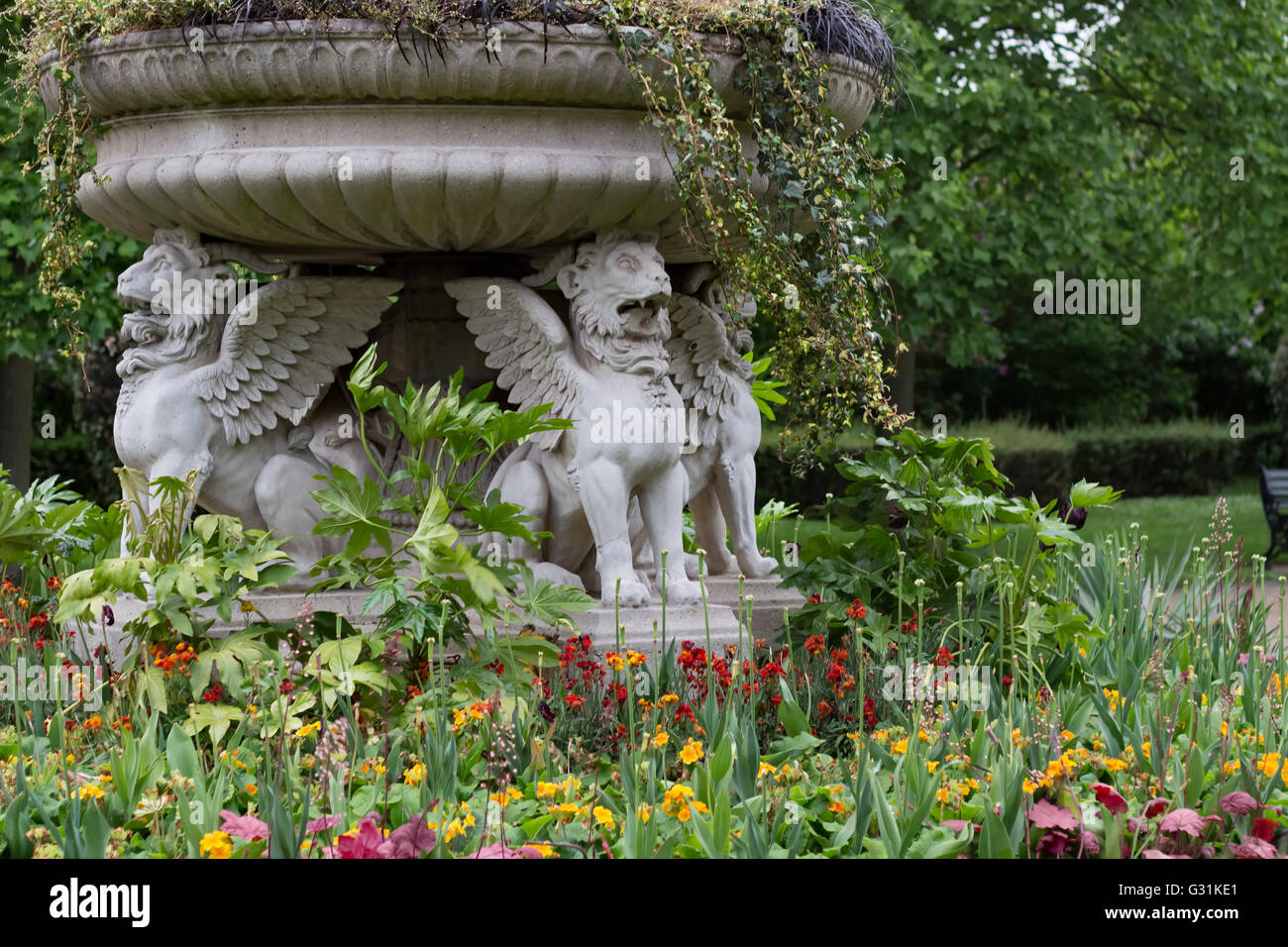 London, England - May 19, 2016: Stone winged lions among flowers in Regent's Park in London, England. - Stock Image