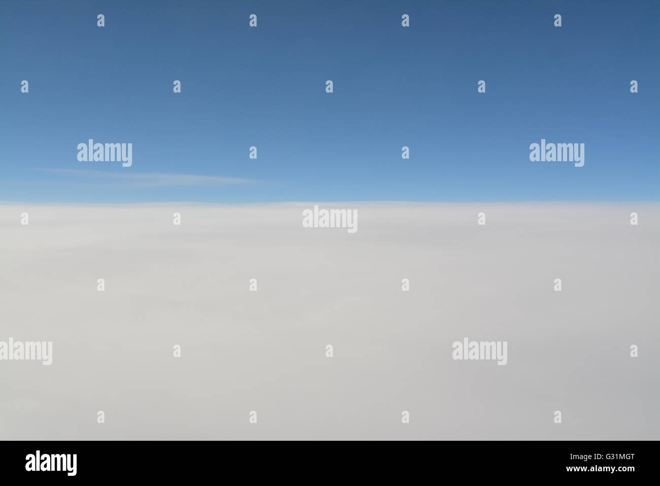 blue sky above white clouds background - view from a plane - Stock Image