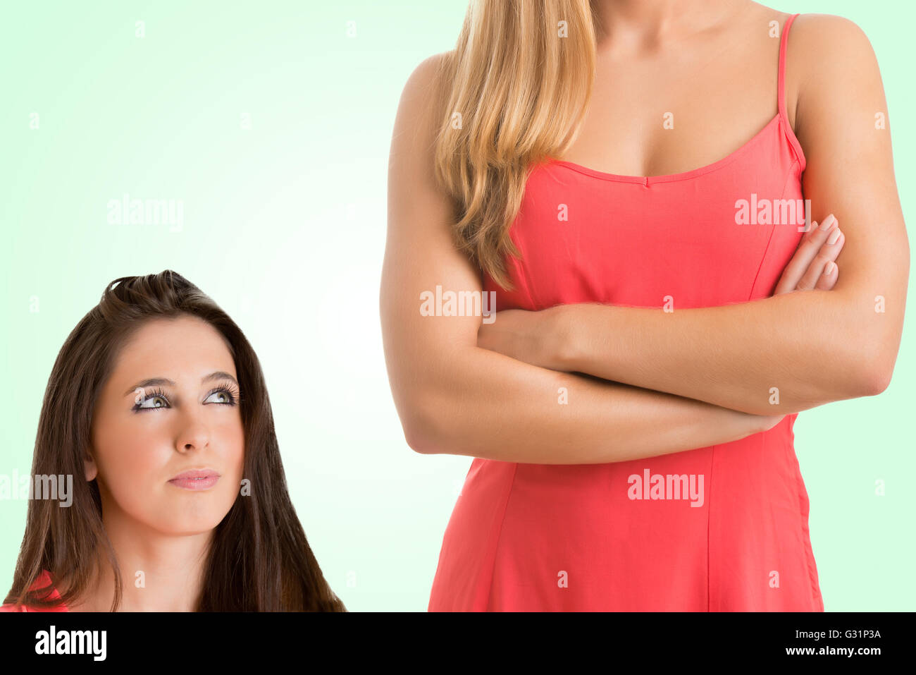 Height difference between two women in a green background - Stock Image