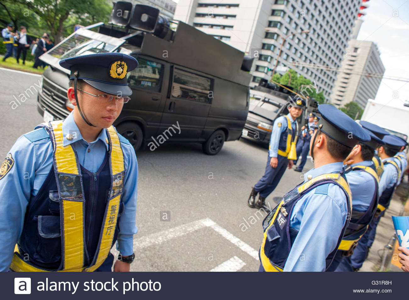 Japanese police form a cordon between ultra-nationalist loudspeaker trucks and participants of the 'Change Japan's - Stock Image