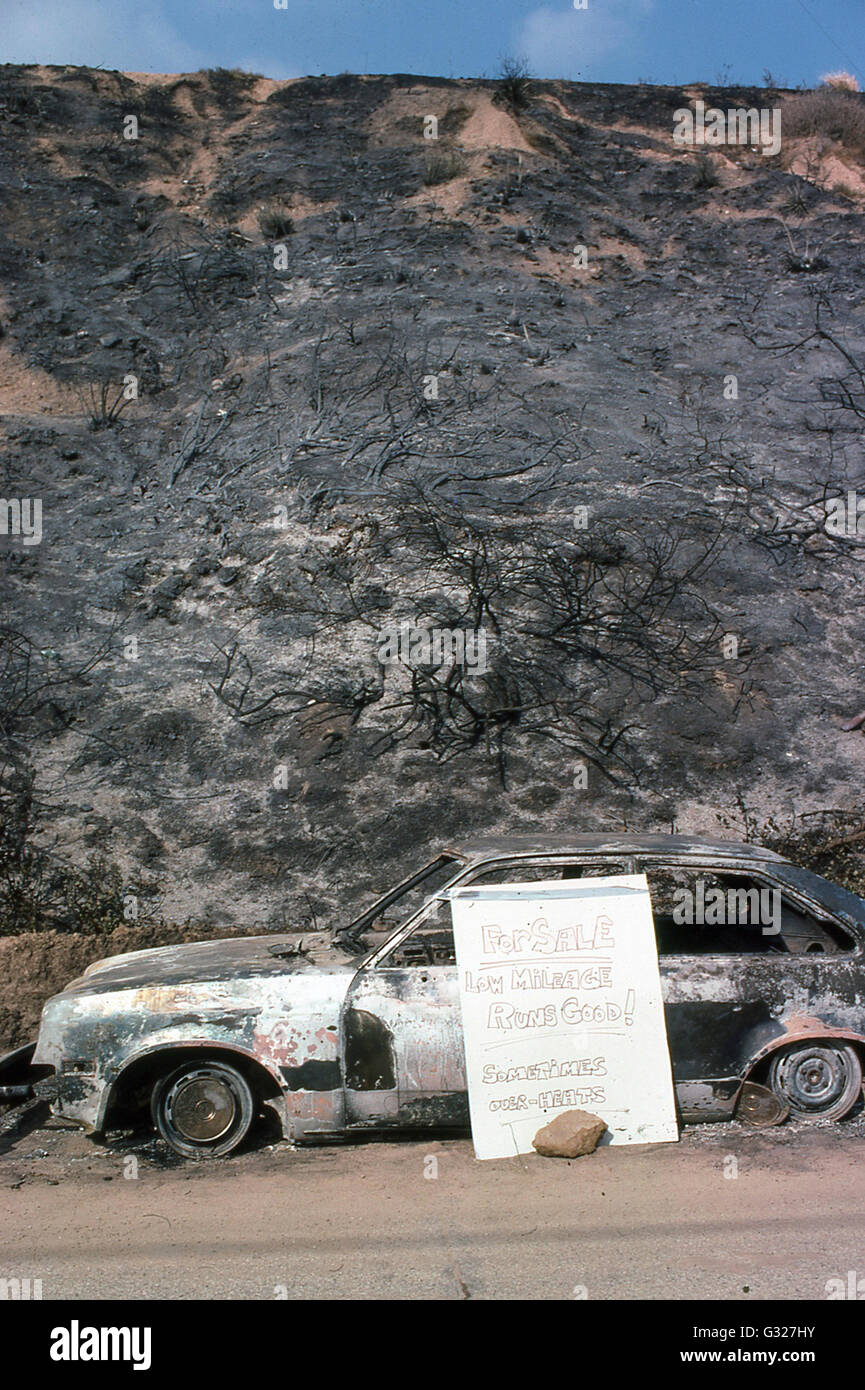 charred hills and burned out automobile for sale after Malibu fire in 1970s Malibu beach community Los Angeles California - Stock Image