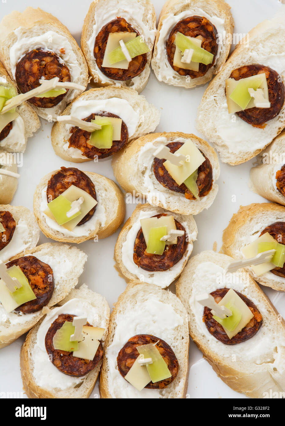 Tasty canapes with butter, sausage, cheese and paprika. Food theme. Catering theme. Refreshments for guests. Sticks - Stock Image