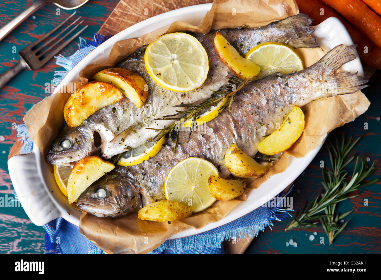 An oven roasted trout in a casserole on a rustic table. With carrots and potatoes on the side. - Stock Image