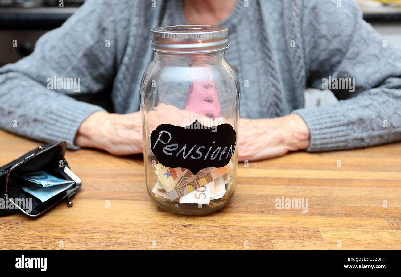 An elderly woman with a money filled jar labelled with the dutch word for pension - Stock Image