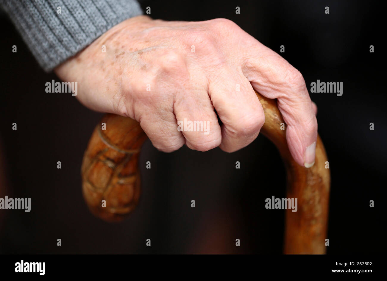 A hand of an elderly woman on a cane - Stock Image