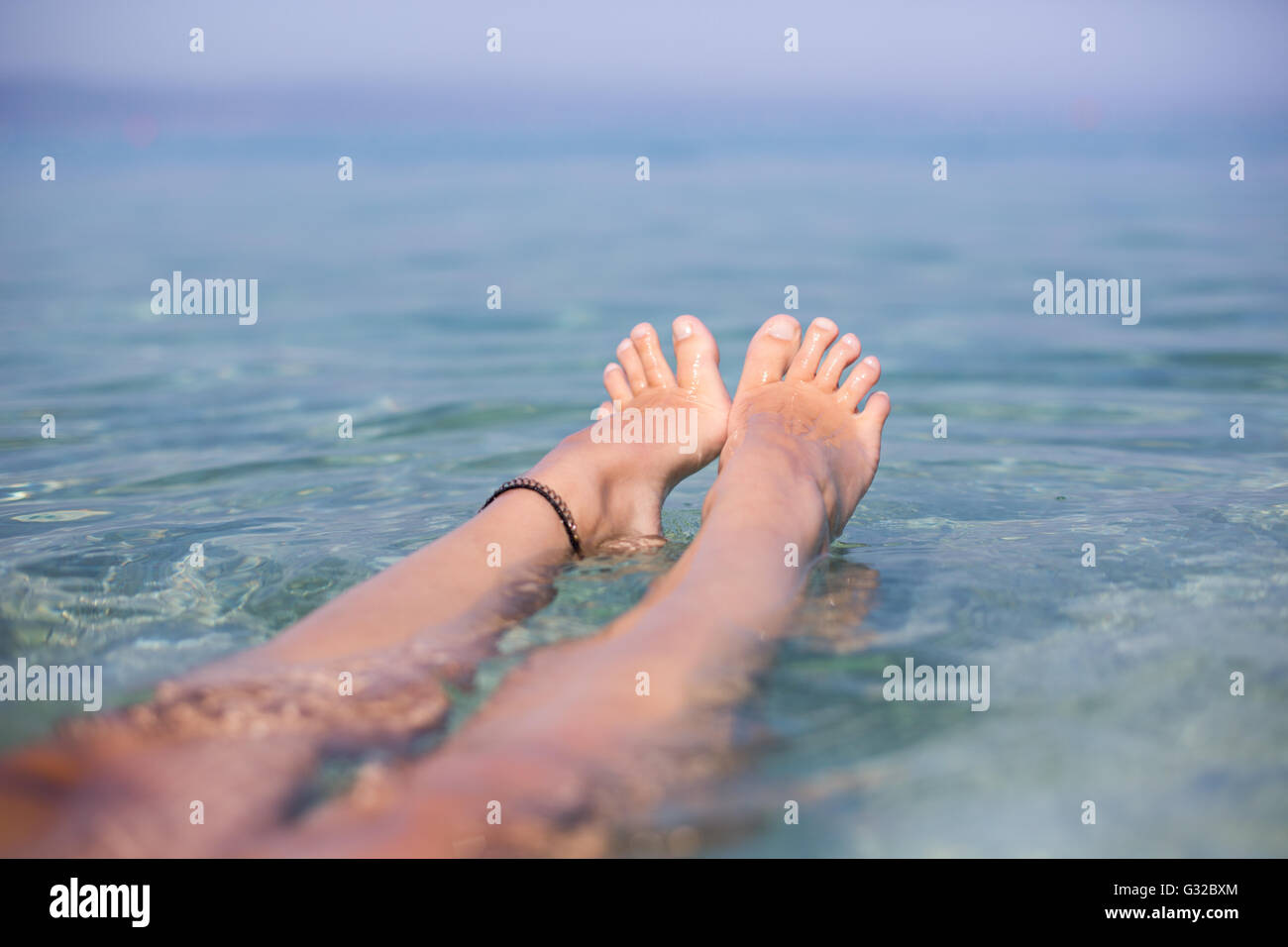 summer, beach, leisure and body part concept - closeup of woman feet on the beach - Stock Image