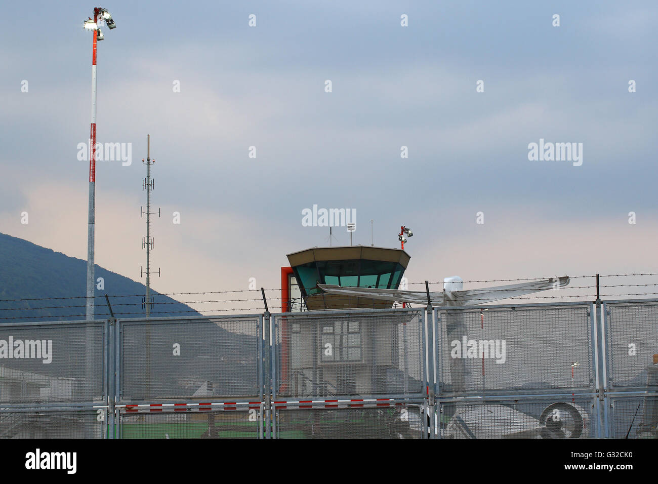 Small international airport with jet plane, control tower, safety barb wire fence and lighting equipment - Stock Image