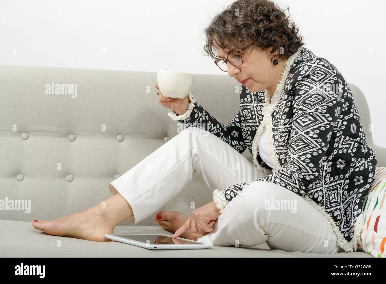 a beautiful mature woman with a tablet on the sofa Stock Photo