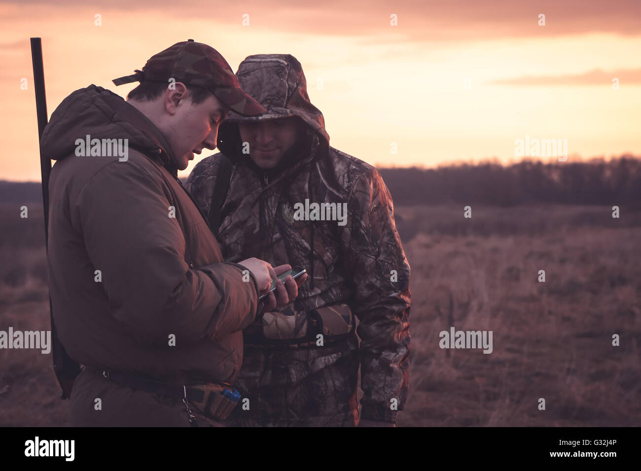 Hunters spot their position via mobile phone  in rural field during hunting season - Stock Image
