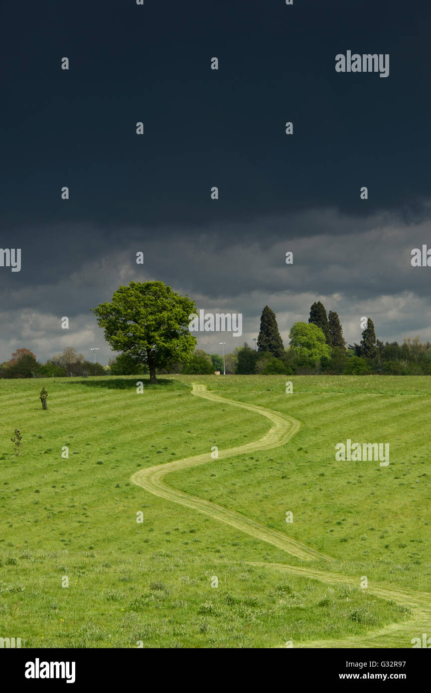 Footpath lit up against a dark stormy sky through an Oxfordshire field. Banbury, Oxfordshire, England - Stock Image