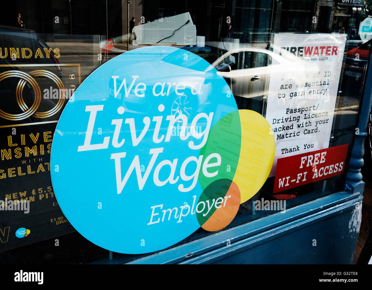 Sign in pub window stating that employees are paid a Living Wage in Glasgow, Scotland, United Kingdom - Stock Image