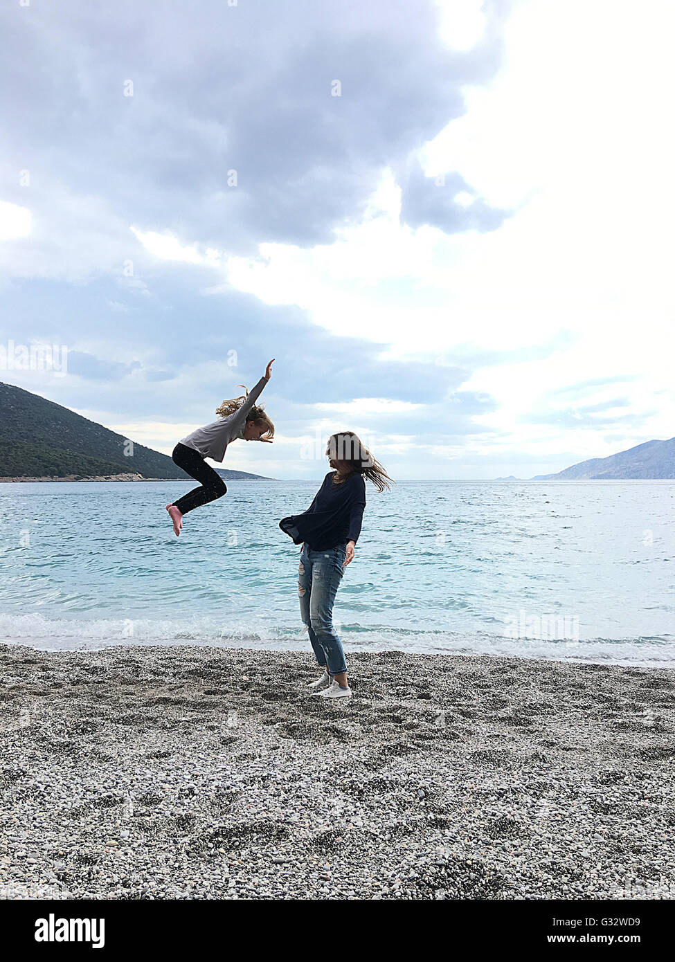 Two girls messing about on the beach - Stock Image