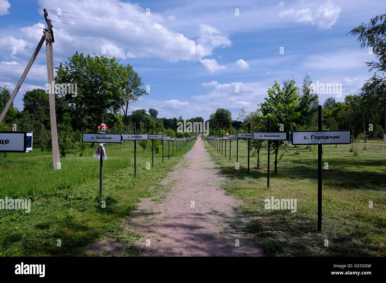 A man walks past the plates with names of abandoned villages at the monument to the Chernobyl nuclear disaster in - Stock Image