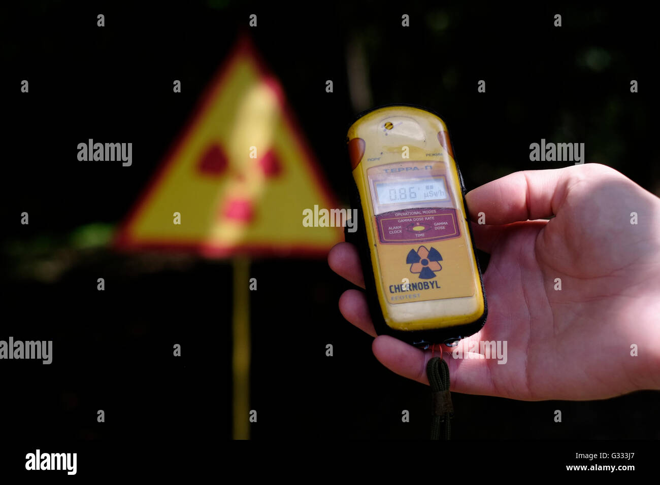 A person measures radioactivity with a geiger counter inside the Chernobyl Exclusion Zone in Ukraine on 04 June - Stock Image