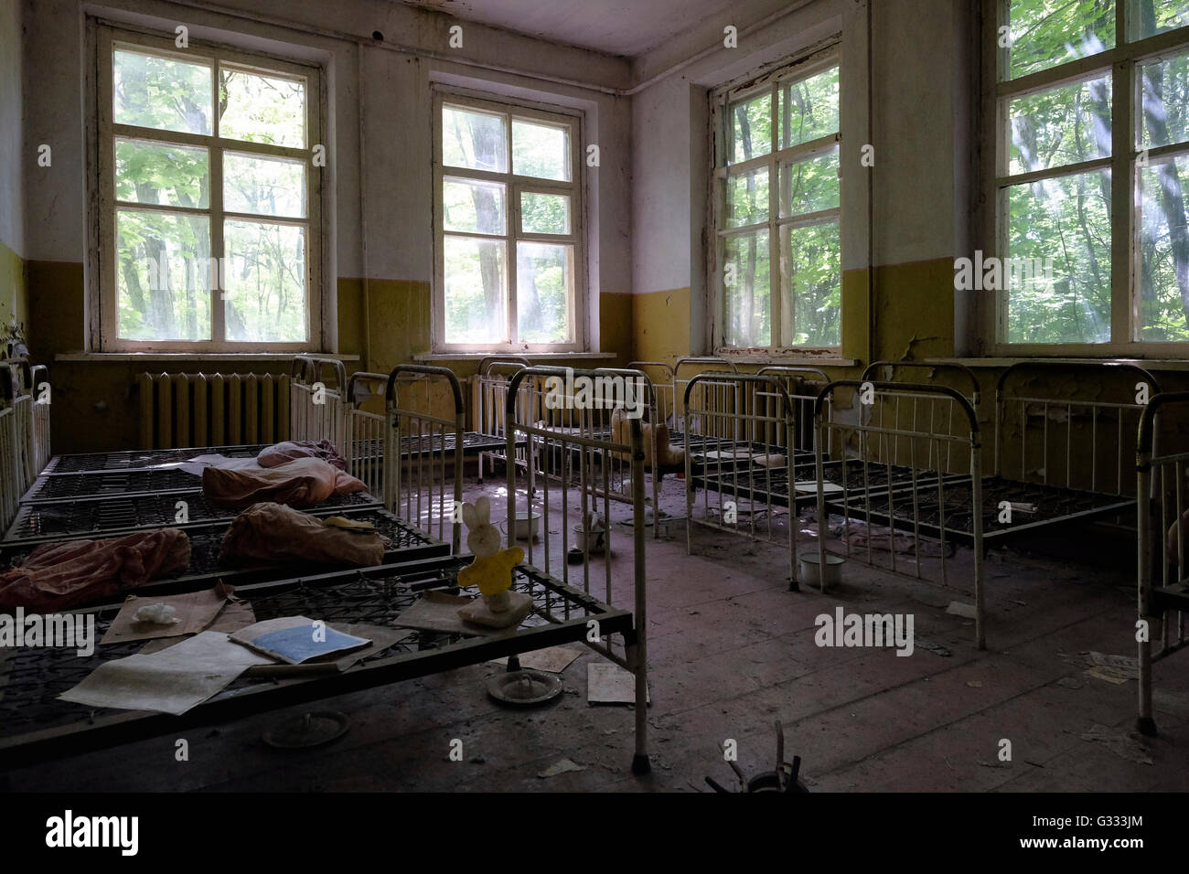 Children's beds stand in the abandoned kindergarten of the deserted village of Kopachi located inside the Chernobyl - Stock Image