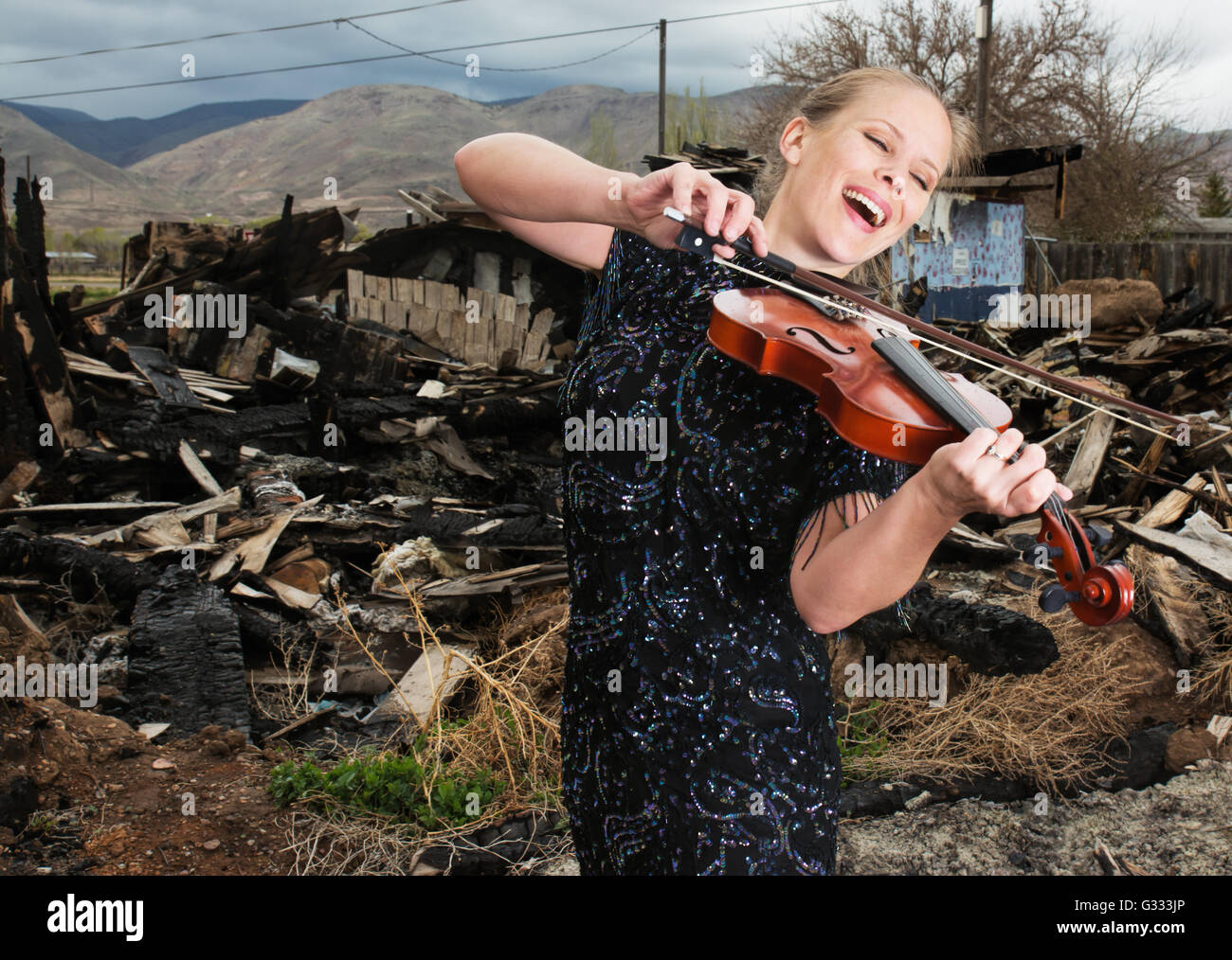 Woman playing a fiddle in front of burnt ruins. - Stock Image
