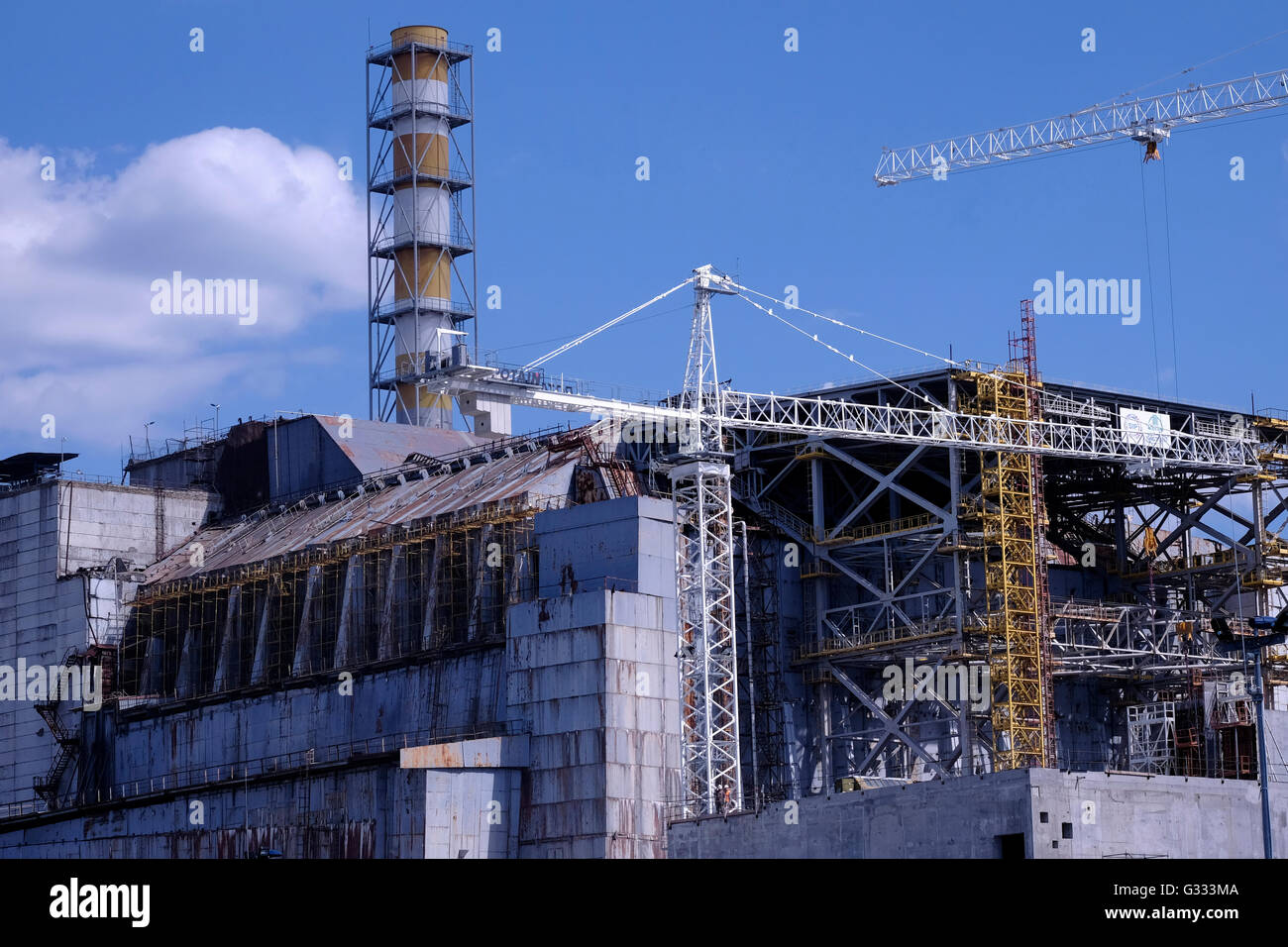 View of the concrete sarcophagus covering the damaged Reactor 4 of the former nuclear power plant located inside - Stock Image