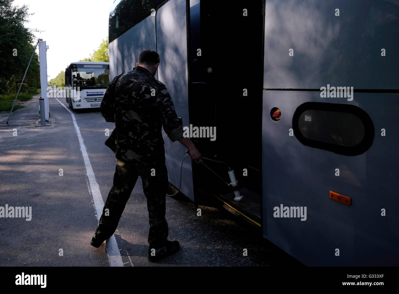 A bus is checked for radiation by a security guard in Leliv checkpoint after leaving the contaminated area of the - Stock Image