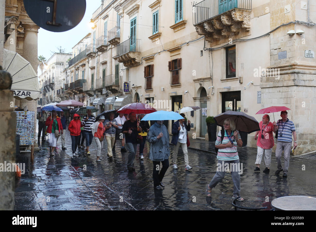 Noto, Italy, tour group makes when it rains a trip through the city - Stock Image