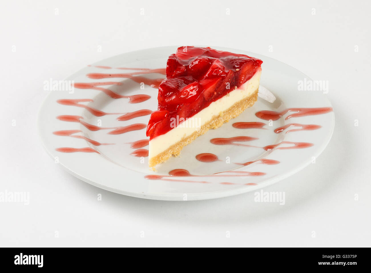Delicious cheesecake with strawberry jelly and jam on the plate on white background. Close up side view. - Stock Image