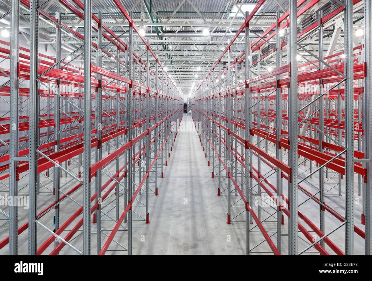 Industrial racks pallets shelves in huge empty warehouse interior. Storage equipment. - Stock Image