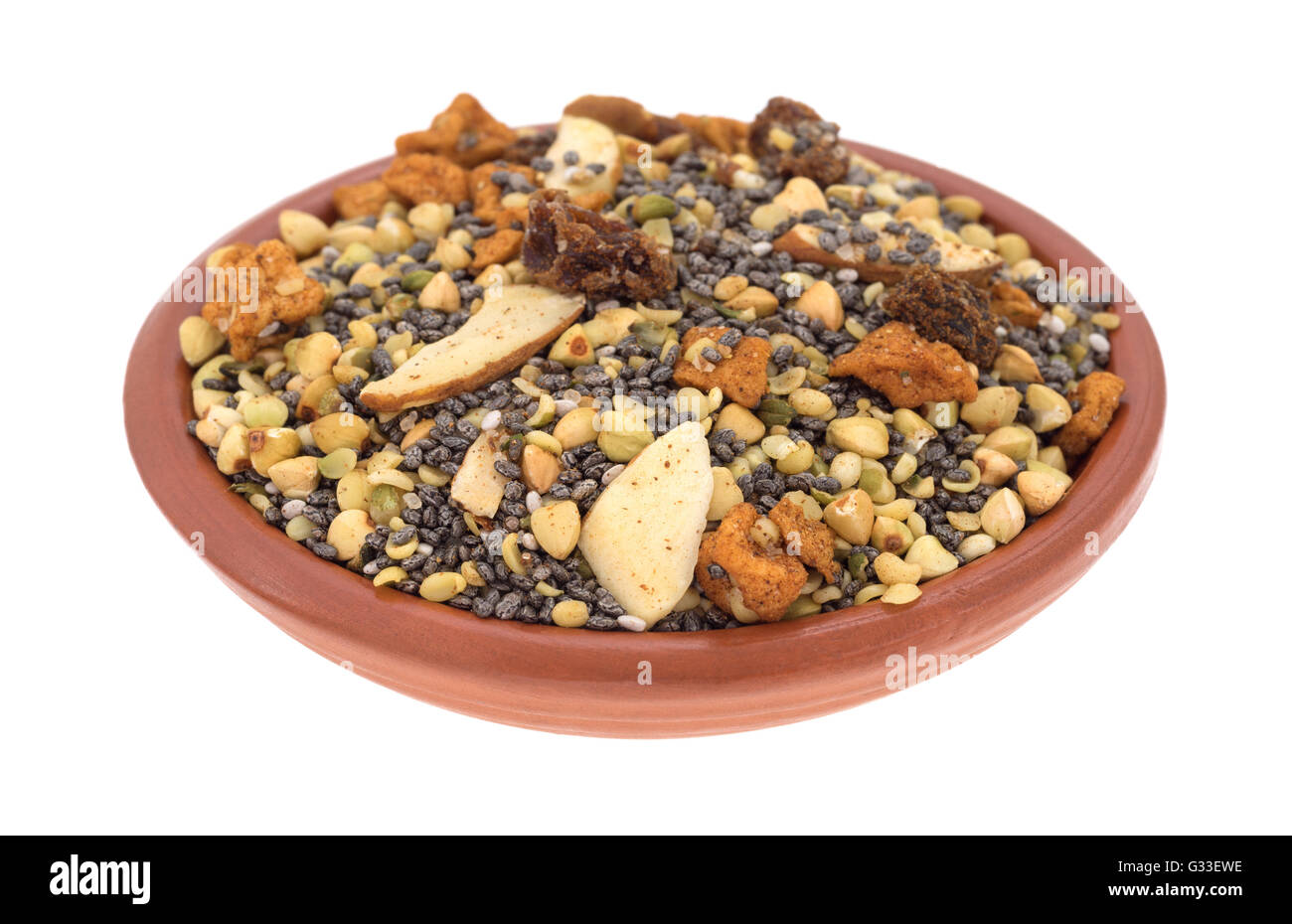 A small bowl filled with dry breakfast cereal consisting of chia seeds, nuts, and dried fruit isolated on a white - Stock Image
