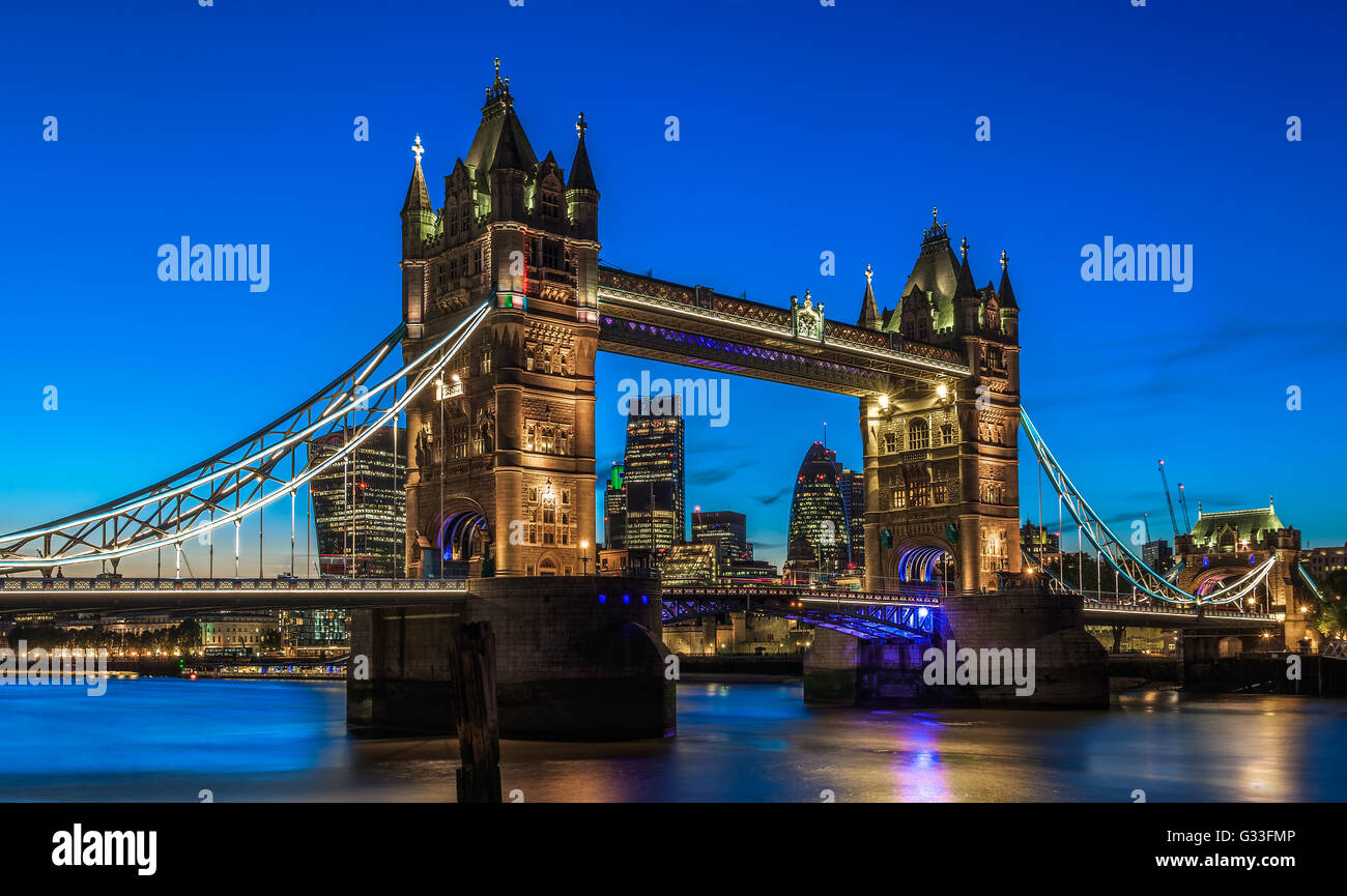 Illuminated Tower Bridge in London after sunset with London's financial district at the background - Stock Image