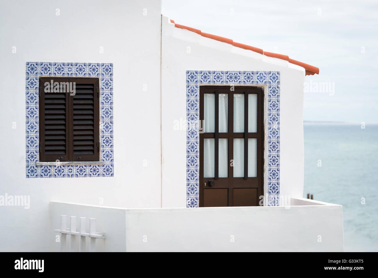 Door and window of house with Azulejos tiles around in Albufeira, Algarve region, Portugal - Stock Image