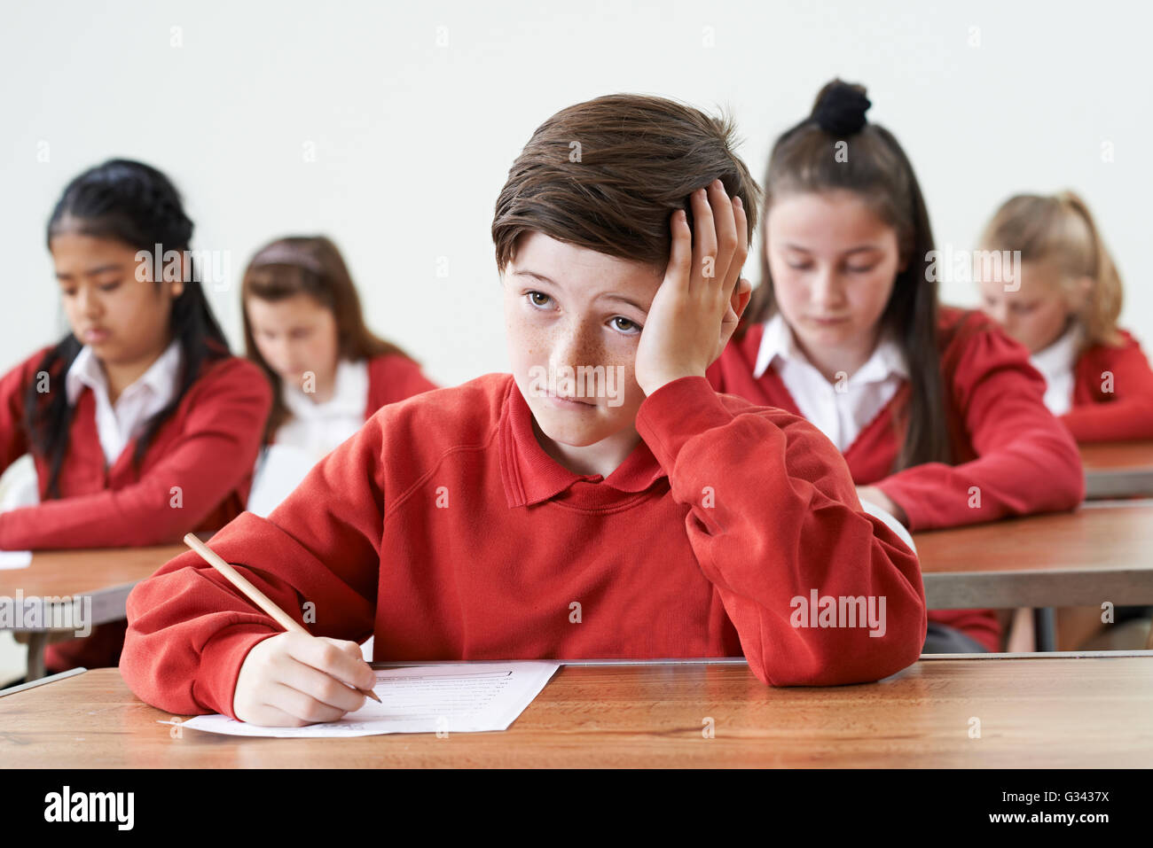 Male Pupil Finding School Exam Difficult - Stock Image