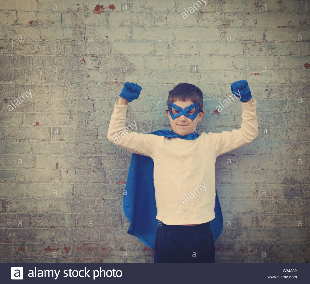 A photo of a vintage child dressed up as a super hero with his strong arms up for a confidence, bravery or imagination - Stock Image