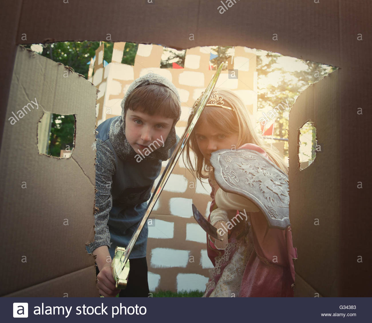 Children are dressed in a knight and princess costumes looking in a door of a cardboard castle for a creative imagination - Stock Image