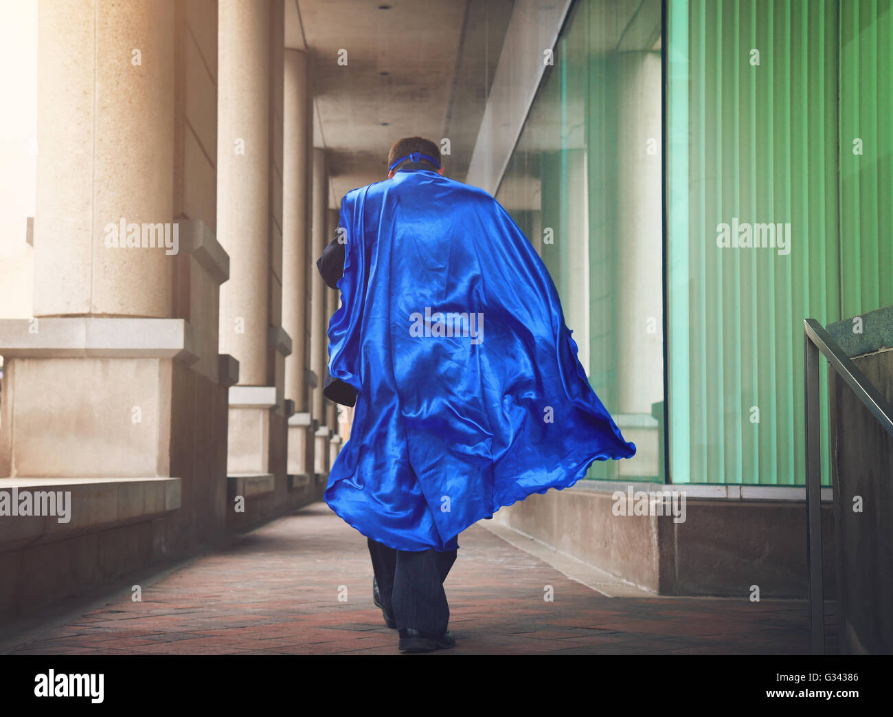 A business man is dressed as a super hero with a blue cape running in the city for a urgent job or leadership concept. Stock Photo