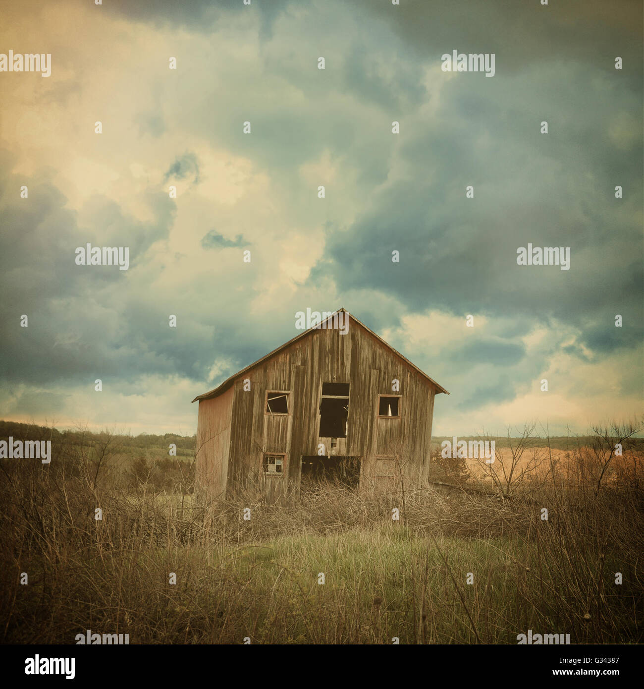 An old abandoned farm house is in the country with scary clouds in a field for a destruction, barn or scary concept. - Stock Image