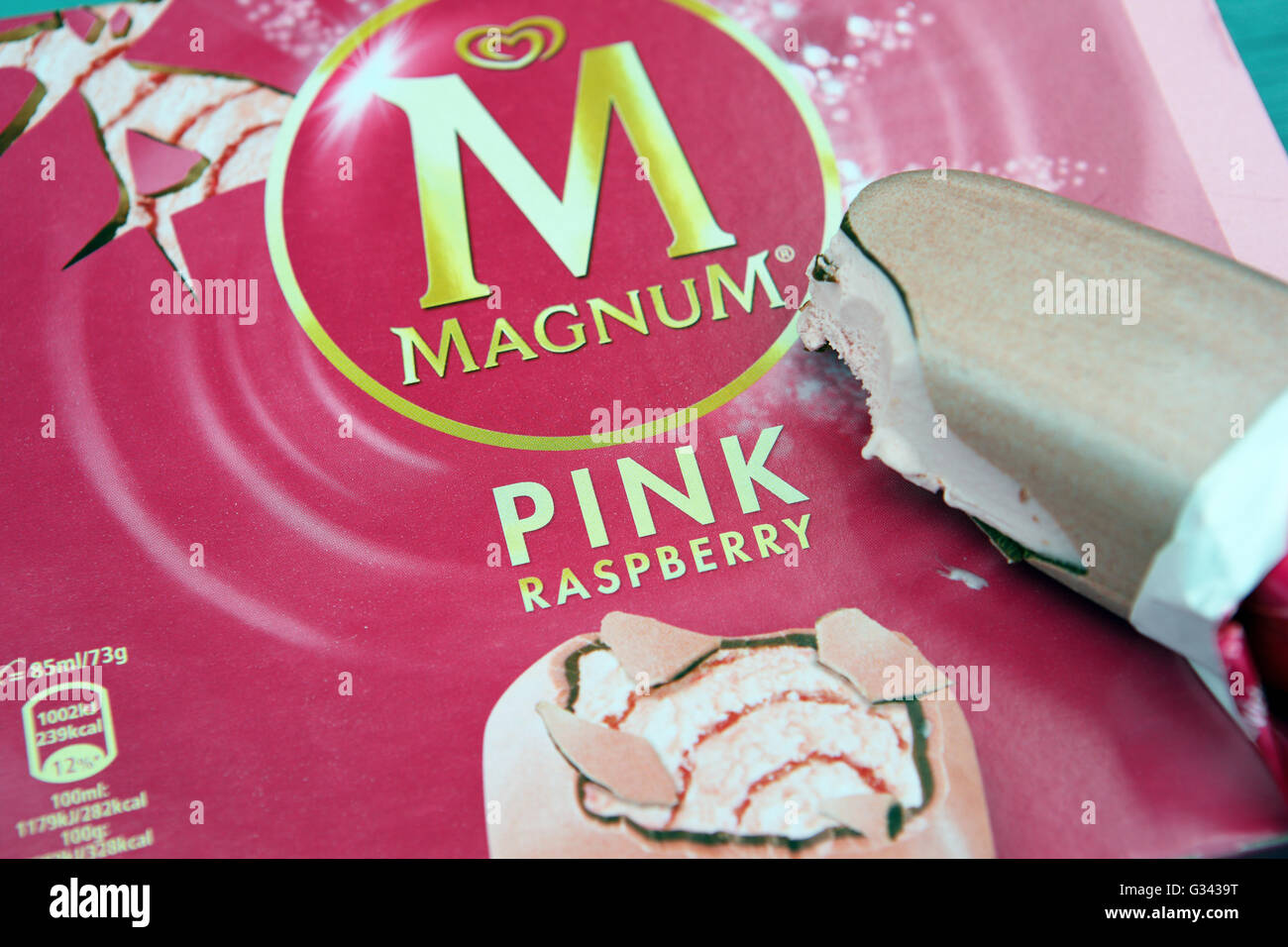 A Magnum Ice cream lolly with a bite out of it, in pink raspberry flavour. - Stock Image