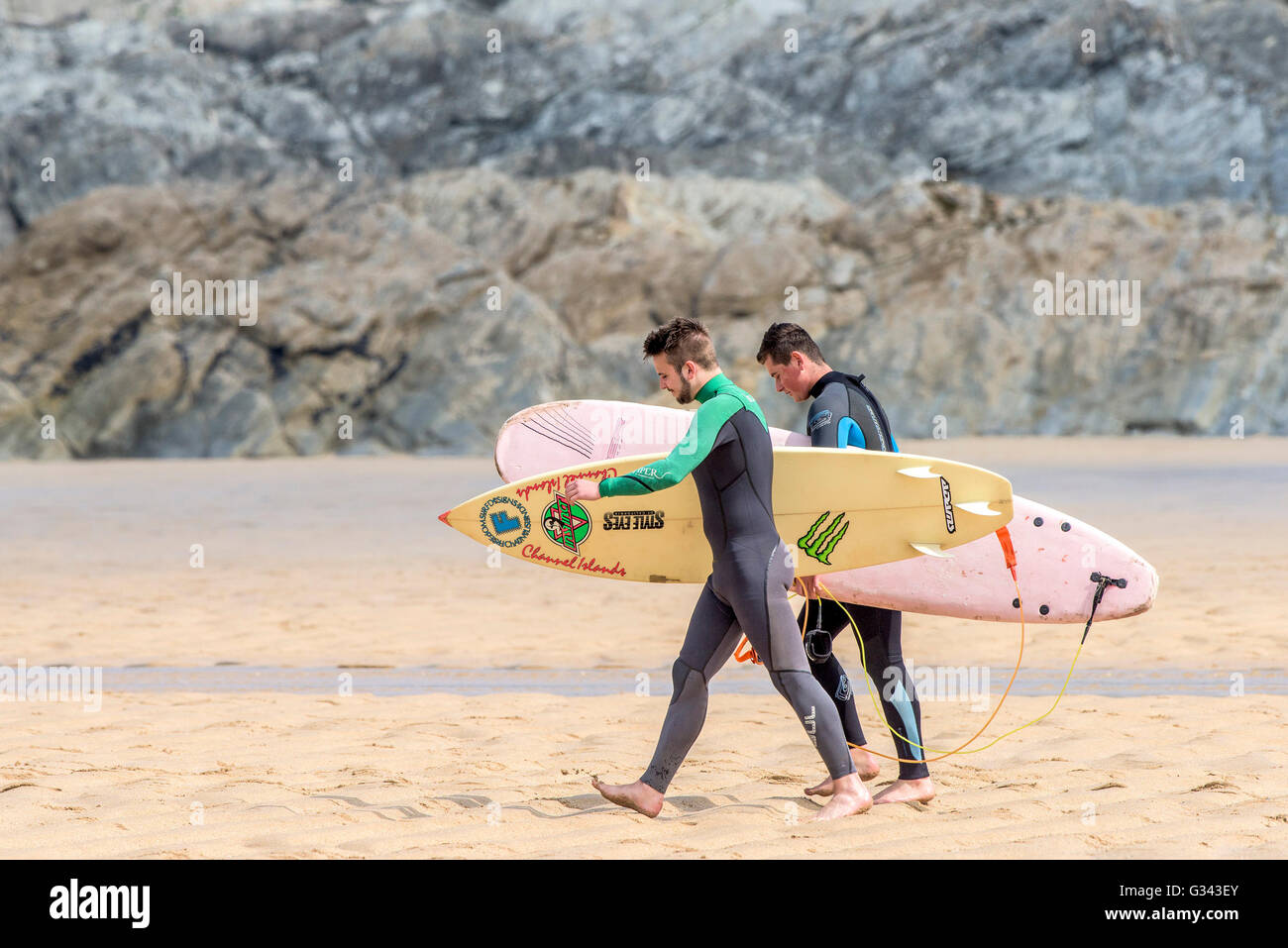 Two surfers walking to the sea at Fistral in Newquay, Cornwall. - Stock Image