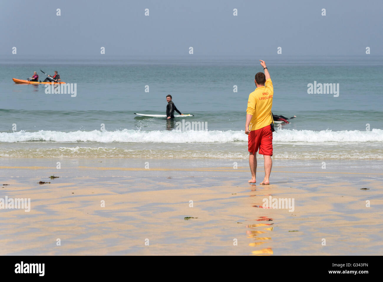 A RNLI Lifeguard instructing holidaymakers to move to a safer area on Fistral in Newquay, Cornwall. UK. - Stock Image