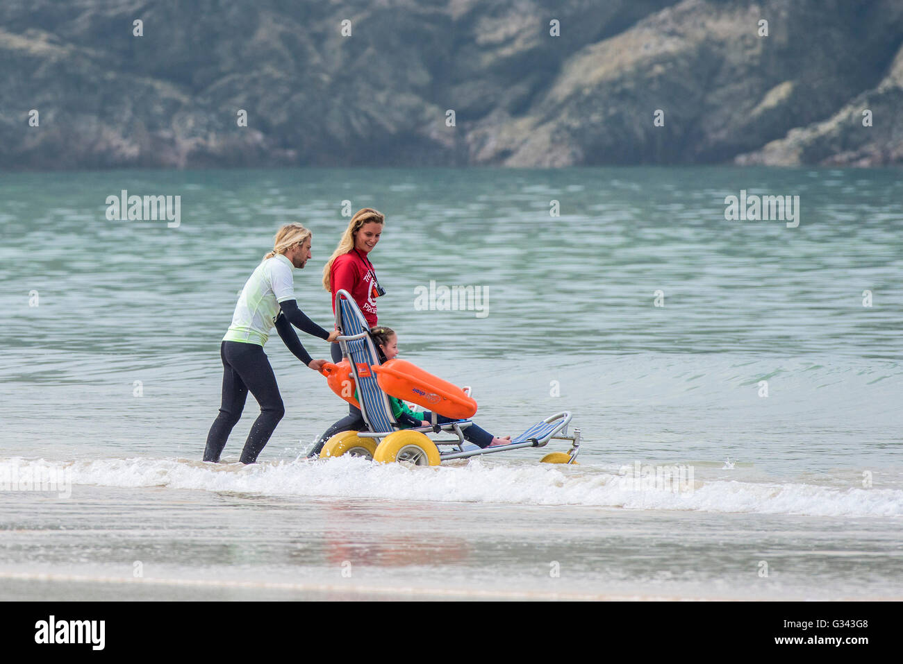 A disabled child using an amphibious wheelchair at Fistral Beach in Newquay, Cornwall. - Stock Image