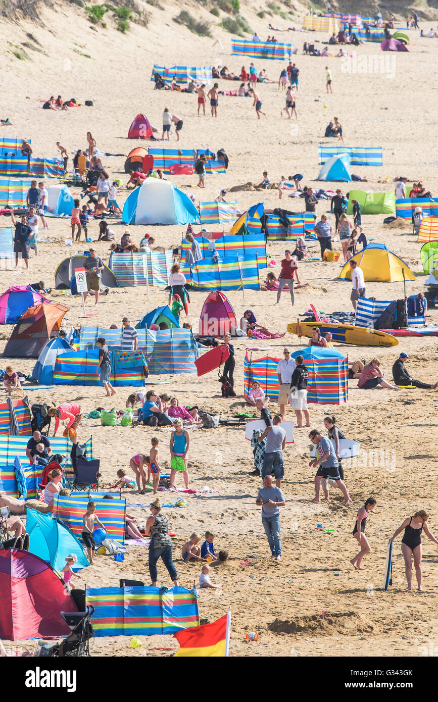 Holidaymakers enjoy the sunny weather on Fistral Beach in Newquay, Cornwall. - Stock Image