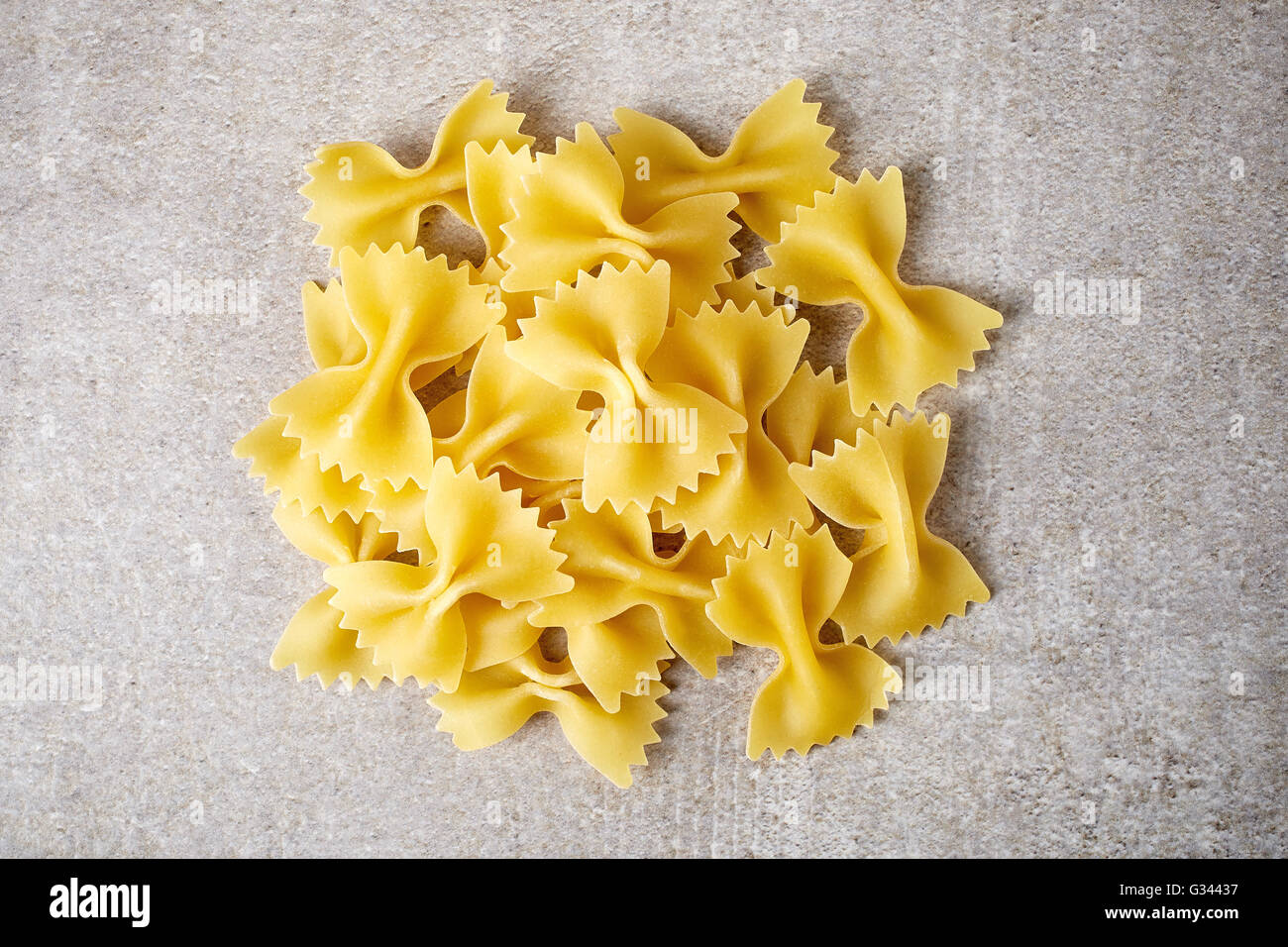 Bow tie pasta on stone table, top view - Stock Image
