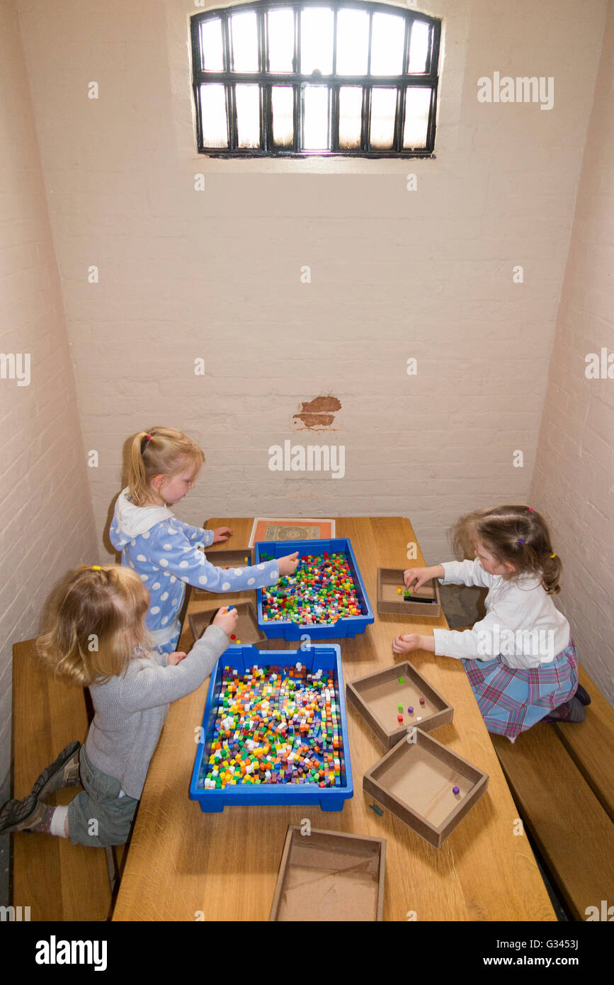 Tourist children / kid / kids / young child play with games in a Victorian gaol / jail prisoner cell in Lincoln - Stock Image