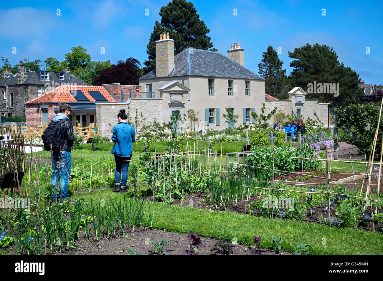 Visitors to the Royal Botanic Gardens in Edinburgh inspect herb and vegetable plots with the Botanic Cottage in - Stock Image