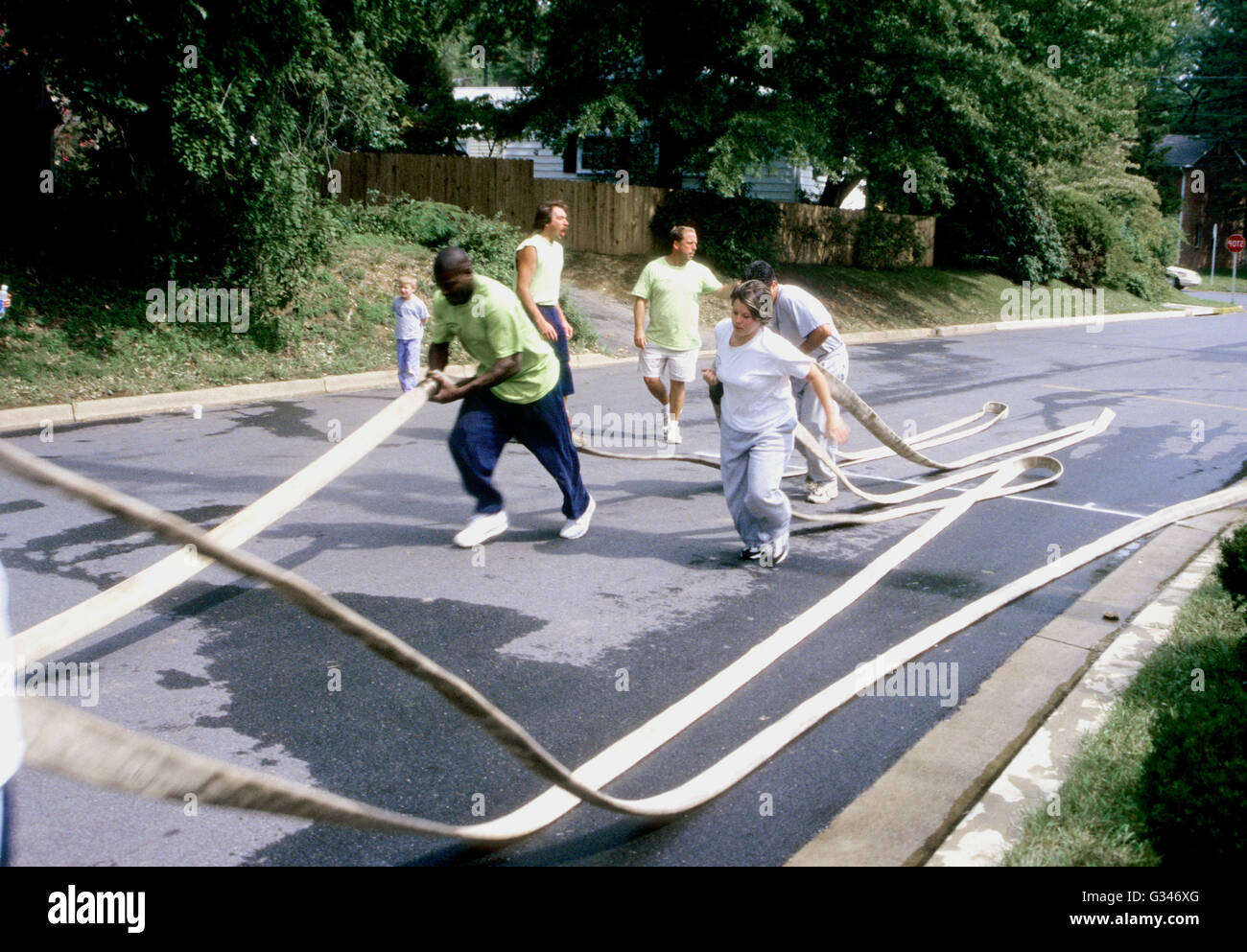 volunteer firefighters drag hoses during cleanup after a fire - Stock Image