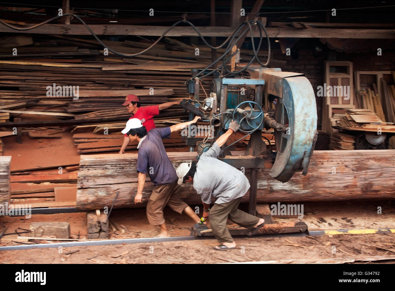 Three woodworker try to push cumbersome machine to split section of a tree trunk into plank at sawmill. June 18, - Stock Image