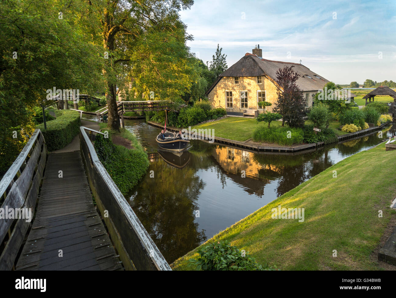 Giethoorn, Netherlands. Boat in the Dorpsgracht or Village Canal with converted farmhouse on island with private - Stock Image